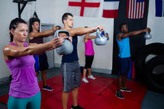 Young athletes lifting kettles Stock Photos