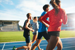 Young athletes running on race track in stadium. Rear view of young people running together on race track. Young athletes practicing a run on athletics stadium Royalty Free Stock Image