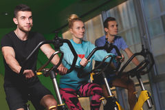 Young athletes in sport clothes. Young athletes on stationary bike in fitness center in sport clothes Royalty Free Stock Photography