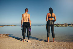 Young athletes standing on beach preparing for triathlon Stock Photography