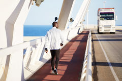 Young athletic afroamerican goes after jogging on the bridge Stock Image