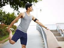 Young athletic asian man stretching leg outdoors royalty free stock photos
