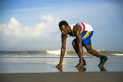Young athletic and attractive black African American runner man doing running workout training on desert beach in fitness and royalty free stock image
