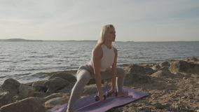 Young athletic beautiful woman with dumbbells in hands on the background of the sea. Fitness girl doing exercises with stock video