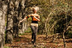 A young athletic blond hair woman runs jumping in a good mood in the park. A young athletic blond hair woman runs jumping in the park between the trees. The Stock Photos