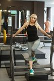 Young athletic blonde is leaning on a barbell and looking at the camera in the gym, the concept of a healthy sports life stock photo