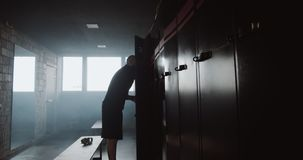 Young athletic Caucasian man changing in dark gym locker room preparing to extreme workout. Motivation and courage. Young athletic Caucasian man changing in stock video footage