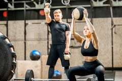 Couple training in the crossfit gym. Young athletic couple in black sports wear training with weights and ball in the crossfit gym Royalty Free Stock Photos