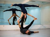 Young athletic couple in dark suits practicing acroyoga in studio with mirrors. Balancing in pair royalty free stock photos