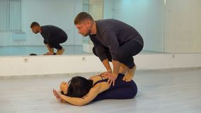 Young athletic couple in dark suits practicing acroyoga in studio with mirrors. Guy is standing on girls back, Balancing stock footage