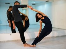 Young athletic couple in dark suits practicing pair yoga in studio with mirrors. Balancing in pair stock photo