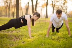 Young athletic couple doing push up outdoors. Athletic family engaged in sports on nature. Sport concept. royalty free stock photography