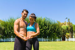 Young athletic couple in sportswear measuring Stock Images