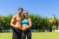 Young athletic couple in sportswear measuring Royalty Free Stock Photography