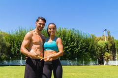 Young athletic couple in sportswear measuring. Delighted young athletic couple in sportswear measuring their waistline after a workout at the park. Healthy Stock Photos