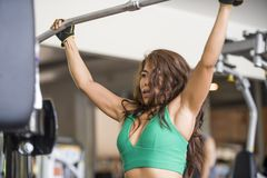 Young athletic and determined Asian Indonesian woman working weights using chest bodybuilding gym machine at fitness club stock images