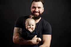 Young athletic father with adorable baby on black background. Handsome athletic men with adorable funny infant baby looking at camera on black background stock images