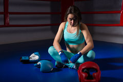 Young athletic female boxer sitting near lying boxing gloves and. Helmet in regular boxing ring in a gym Stock Image