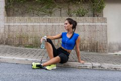Young athletic female resting after running exercise, listening to music in earphones, holding a bottle of water. Sitting on a sidewalk on city street Stock Photo