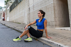 Young athletic female resting after running exercise, listening to music in earphones, holding a bottle of water Royalty Free Stock Photography