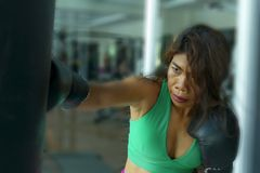 Young athletic and fit attractive Asian fighter woman punching heavy bag with boxing gloves at fight club gym doing hard workout. Sweaty and furious learning royalty free stock photography