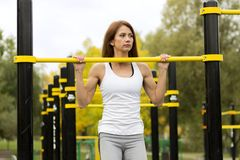 Young athletic fitness woman working out at outdoor gym doing pull ups at sunrise Stock Images