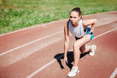 Young athletic girl athlete preparing to run at stadium, outdoors. The concept of healthy lifestyle royalty free stock image