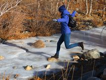A young athletic girl with a backpack behind her back overcomes a frozen river jumping from stone to stone. The ice is still thin, the danger of failure Royalty Free Stock Photography