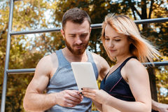 Young athletic girl and bearded man browsing the internet on tab Stock Photo