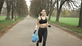 Young athletic girl in a black sport suit and gloves runs through green summer park with a trash bag in her hand. Young athletic girl in a black sport suit runs stock video footage