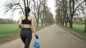Young athletic girl in a black sport suit runs through green summer park with a trash bag in her hand, plogging concept. Young athletic girl in a black sport stock video footage