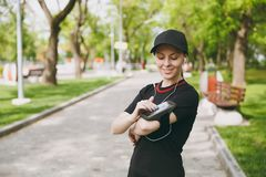 Young athletic girl in black uniform with headphones listening music, looking on mobile phone using application, app for royalty free stock photo