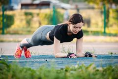 Young athletic girl does exercise plank on sports field in park stock photography