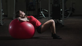 Young athletic girl in the gym. Young, beautiful, sports girl does exercises on a fitball at the gym Stock Photos