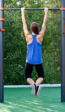 Young athletic girl hanging on the bar. Royalty Free Stock Image