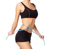 Young athletic girl measuring waist Stock Images