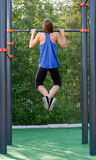 Young athletic girl pulls on the bar. Royalty Free Stock Images