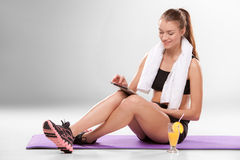 Young athletic girl sitting with laptop in. Young athletic girl sitting with laptop with cocktail isolated on gray background. Pause in training Stock Image