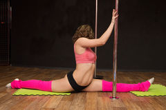 Young athletic girl sitting on the splits near the pole Stock Photos
