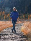 A young athletic girl is standing on a wooden path over the water in the autumn frosty season. stock photos