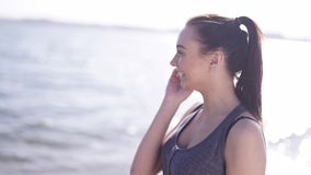 Young athletic girl talking by phone on a beach stock video footage