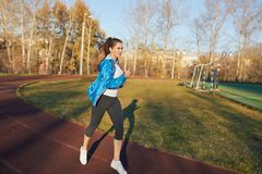 Young athletic girl trains at the stadium. royalty free stock photos
