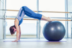 Young and athletic girl using fitness ball in a gym. Stock Photography
