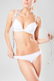 Young athletic girl in white underwear measuring shape Royalty Free Stock Images