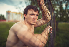 Young athletic guy near the netting Royalty Free Stock Images