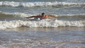 Young athletic guy paddling out at ocean wave and learning to surfing during summer trip on sunny day. Concept of. Vacation or holiday. Close up stock video