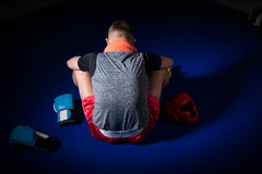 Young athletic male boxer with a towel around his neck sitting b. Ackwards near lying boxing gloves and helmet in regular boxing ring in a gym Royalty Free Stock Image