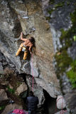 Young athletic male rock climber climbing cliff wall. Copy space on the right. Stock Photos
