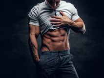 Young athletic male shows six pack ABS. Young athletic male in white shirt shows six pack ABS royalty free stock photography