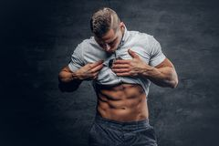 Young athletic male shows six pack ABS. Young athletic male in white shirt shows six pack ABS stock photos